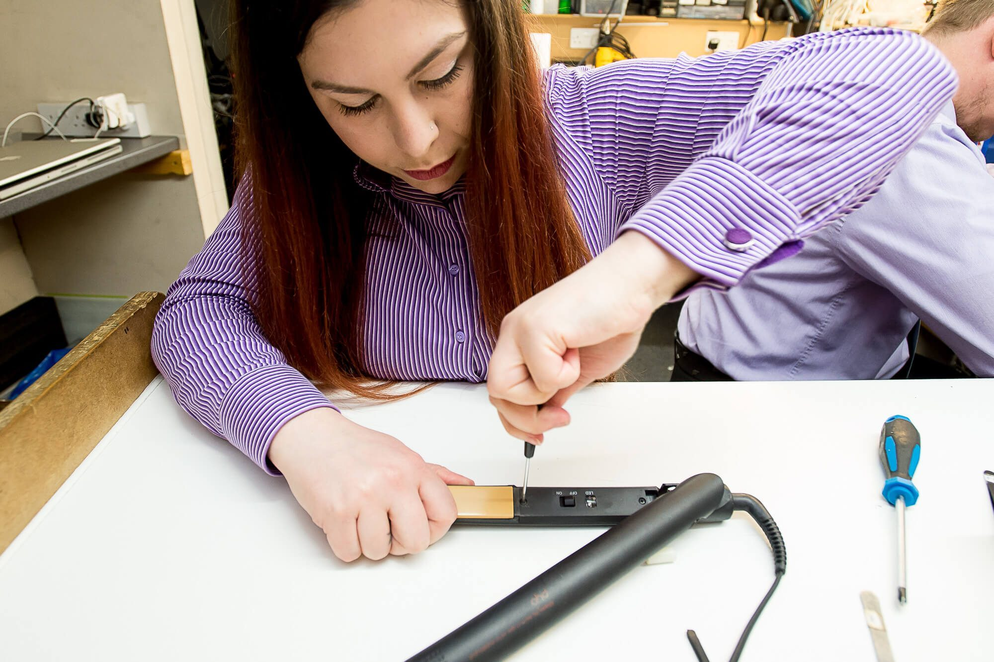 A SimplyFixIt technician fixing a set of GHD hair straighteners.